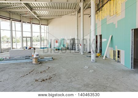 View on indoor construction site of unfinished modern large showroom.
