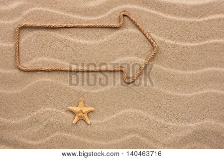 Pointer made of rope and seashell on the sand with place for your text