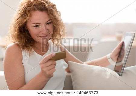 Materialistic view. Pleasant delighted adult smiling woman sitting on the sofa and holding credit card while feeling relaxed