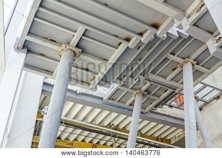 Metal pillars are support to crisscross stairs leading up.