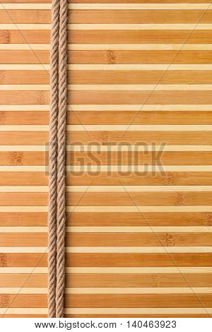 Frame of two smooth ropes lying on a bamboo mat with space for text