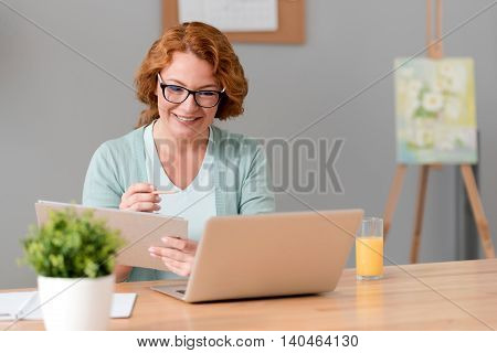 Work with pleasure. Nice delighted cheerful senior woman sitting at the table and holding folder while using laptop