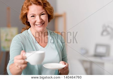 Help yourself. Pleasant positive beautiful smiling woman holding cup and drinking tea while sharing with you