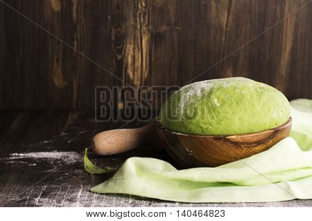 Green spinach dough and ingredients over wooden table. Selective focus. Vintage style