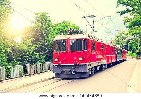 Passenger train moves on the city street at sunset. Chur. Switzerland.