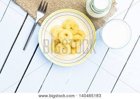 Donut dessert and milk bottle and milk glass  on wooden sky blue table.Meal or breakfast hi-vitamin and calcium.