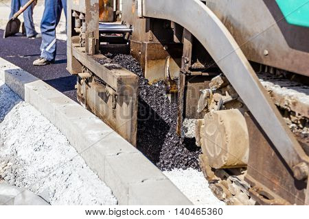 Detail of industrial machinery working with asphalt. Tarmac road laying machine. Asphalt spreader.