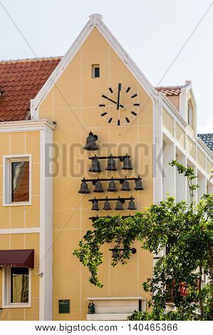 Many bells and clock on a yellow plaster church in Curacao