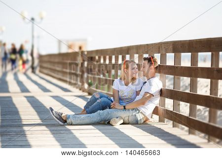 Cheerful couple are sitting by the wooden fence on the beach summer time