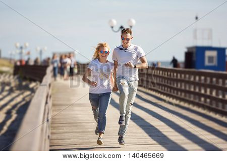 Cheerful couple are running along the boardwalk at summer time