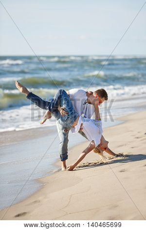 Cheerful couple are making acrobatic dance on the beach summer time