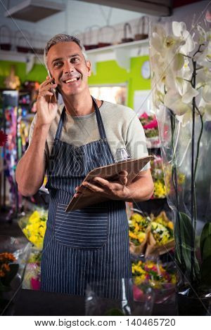 Male florist taking order on mobile phone at his shop