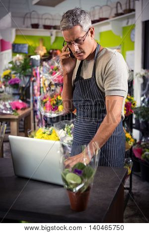 Male florist taking order on laptop at his flower shop
