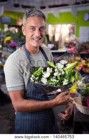 Portrait of happy male florist holding bunch of white flower in vase at his flower shop