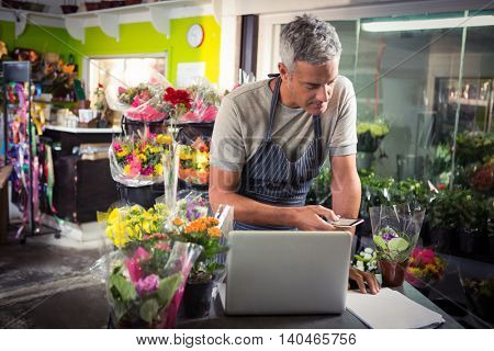 Male florist using mobile phone at his flower shop