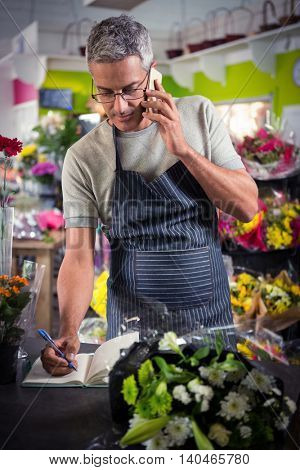Male florist taking order on mobile phone at his flower shop