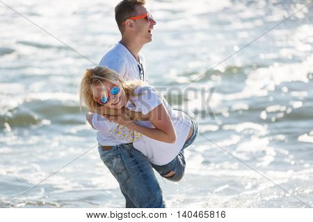 Cheerful couple have fun on the beach summer time