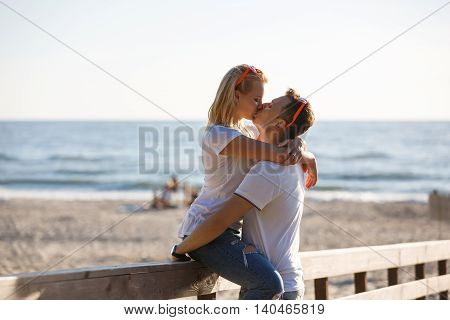Young couple are kissing by the wooden fence on the beach summer time