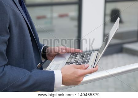 Man businessman holding a laptop outdoors in a formalwear. Clothes and hands