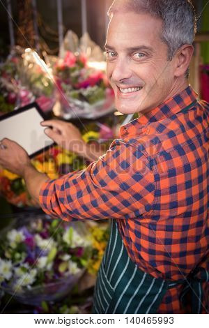 Happy male florist taking photo of flower bouquet on digital tablet at his flower shop