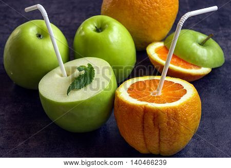 Juicy apples and oranges with tubes for a cocktail. Drink the juice directly from the fruit. Concept - healthy food.