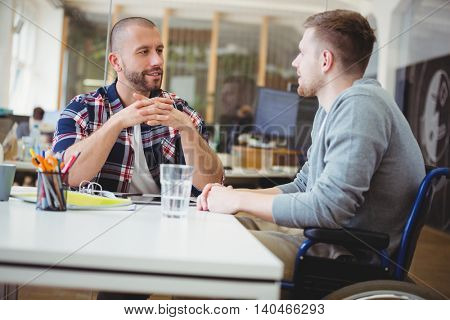Young handicap businessman discussing while sitting with colleague in creative office