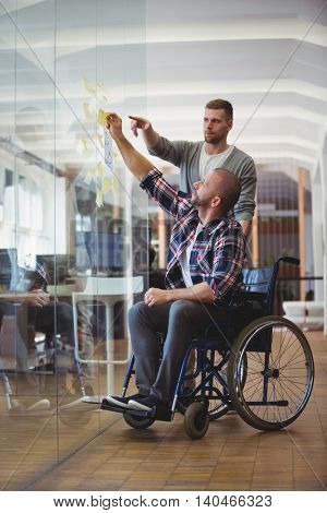Young handicap businessman and colleague sticking adhesive notes on glass window in creative office