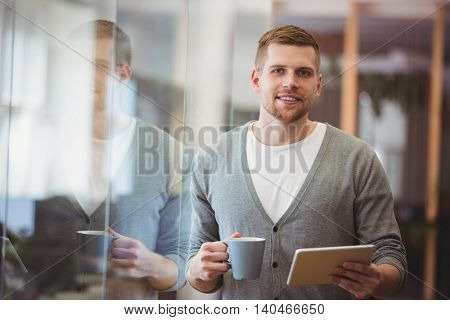 Portrait of businessman holding coffee cup with digital tablet in office