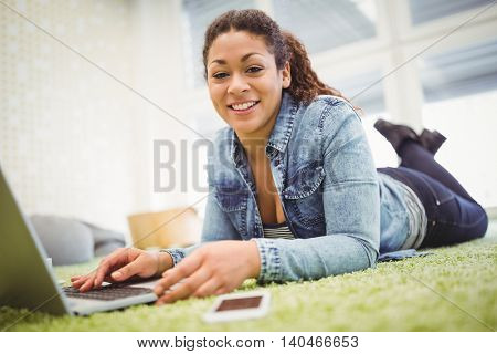 Portrait of businesswoman lying on carpet while using laptop in creative office