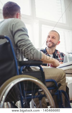 Low angle view of handicap businessman sitting with colleague in creative office