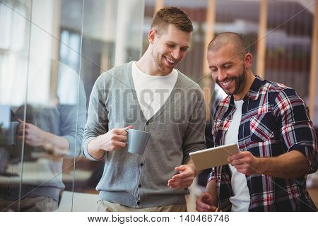 Young businessman with colleague using digital tablet in creative office