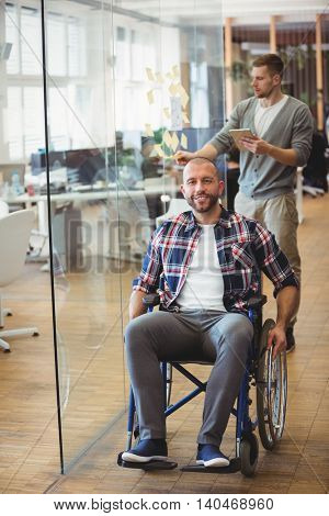 Portrait of smiling handicap businessman with colleague in background at creative office
