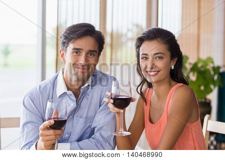 Portrait of couple holding glass of red wine in restaurant
