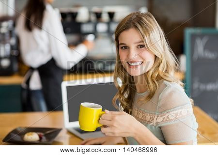 Portrait of smiling woman sitting at cafe having cup of coffee