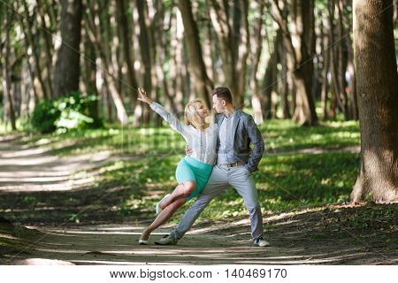 Cheerful couple are dancing in the forest summer time