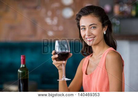Smiling woman sitting in restaurant holding glass of red wine