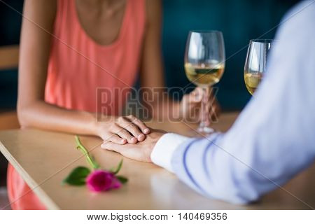 Mid section of couple holding hands while having glass of wine in restaurant