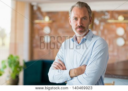Portrait of confident man standing with arms crossed in restaurant