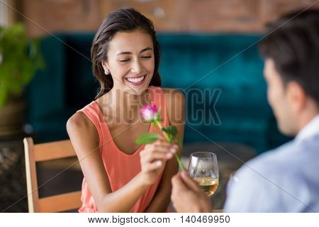 Man giving red rose to woman in restaurant