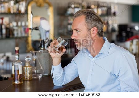 Serious man drinking whiskey at bar counter in restaurant