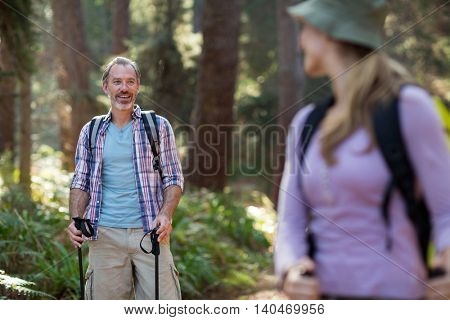 Smiling hiker hiking with trekking poles in forest