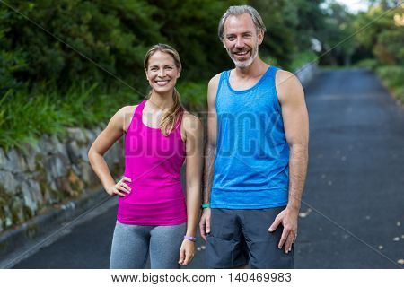 Smiling athletic couple standing on road after jogging