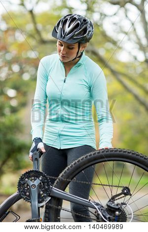 Fit woman repairing her bicycle in countryside