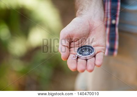 Close-up of hiker holding his compass in the countryside