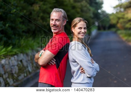 Smiling athletic couple standing back to back on the open road