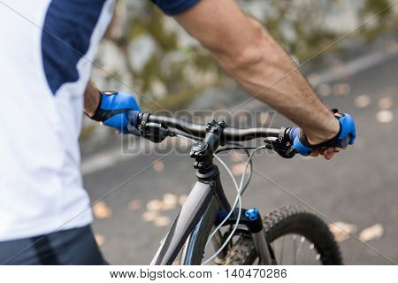 Mid section of man cycling on the road