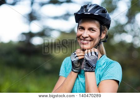 Portrait of smiling female athletic wearing bicycle helmet