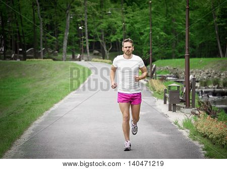 Running fitness man sprinting outdoors in beautiful park.