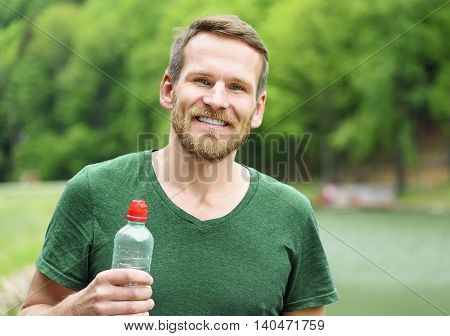 Sportsman with a bottle of water after running outdoors in park.