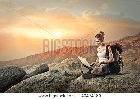 Happy backpacker using a laptop